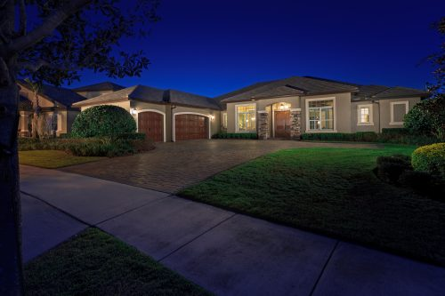 night shot of beautiful new custom home design built by Ayers, a custom homebuilder in the Orlando area